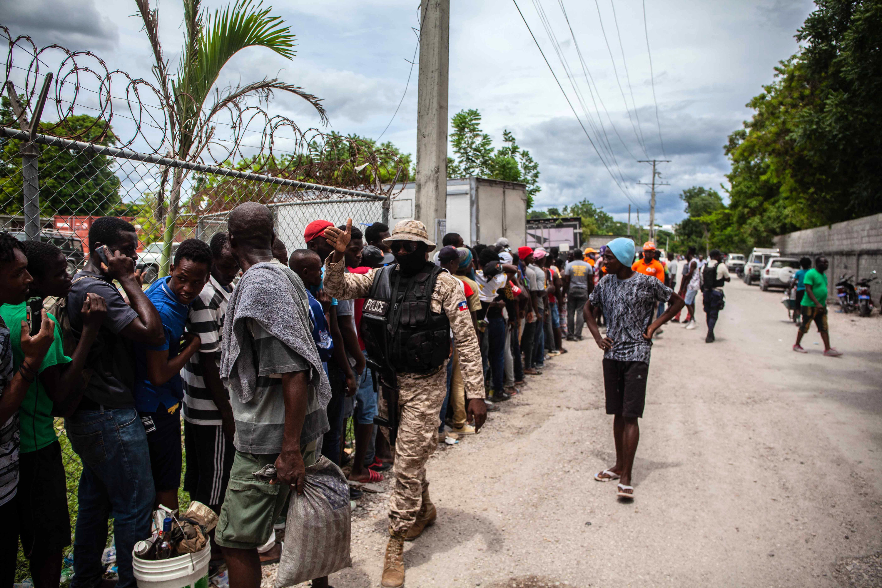 Haitian residents wait in line for food as a police officer walks by