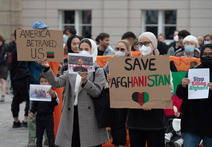 Participants in the rally Humanitarian Airlift Now - Don't Abandon Afghanistan's People stand with placards on the Old Market Square