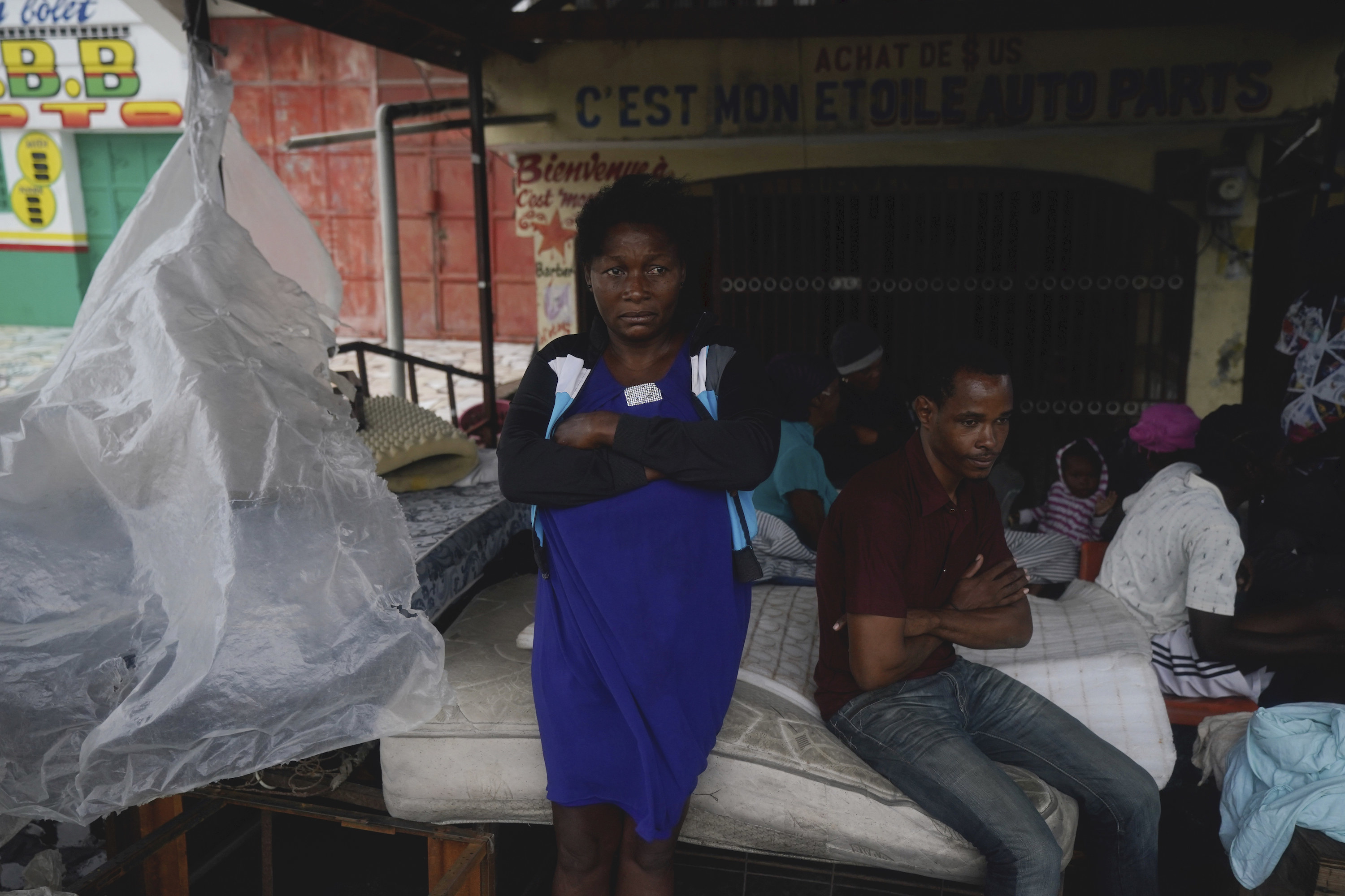 Haitian residents sit and lean against a mattress outside under an awning
