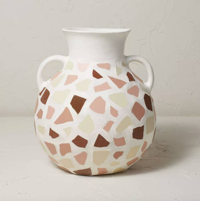a white jug-shaped vase with pink, cream, and brown shapes on it