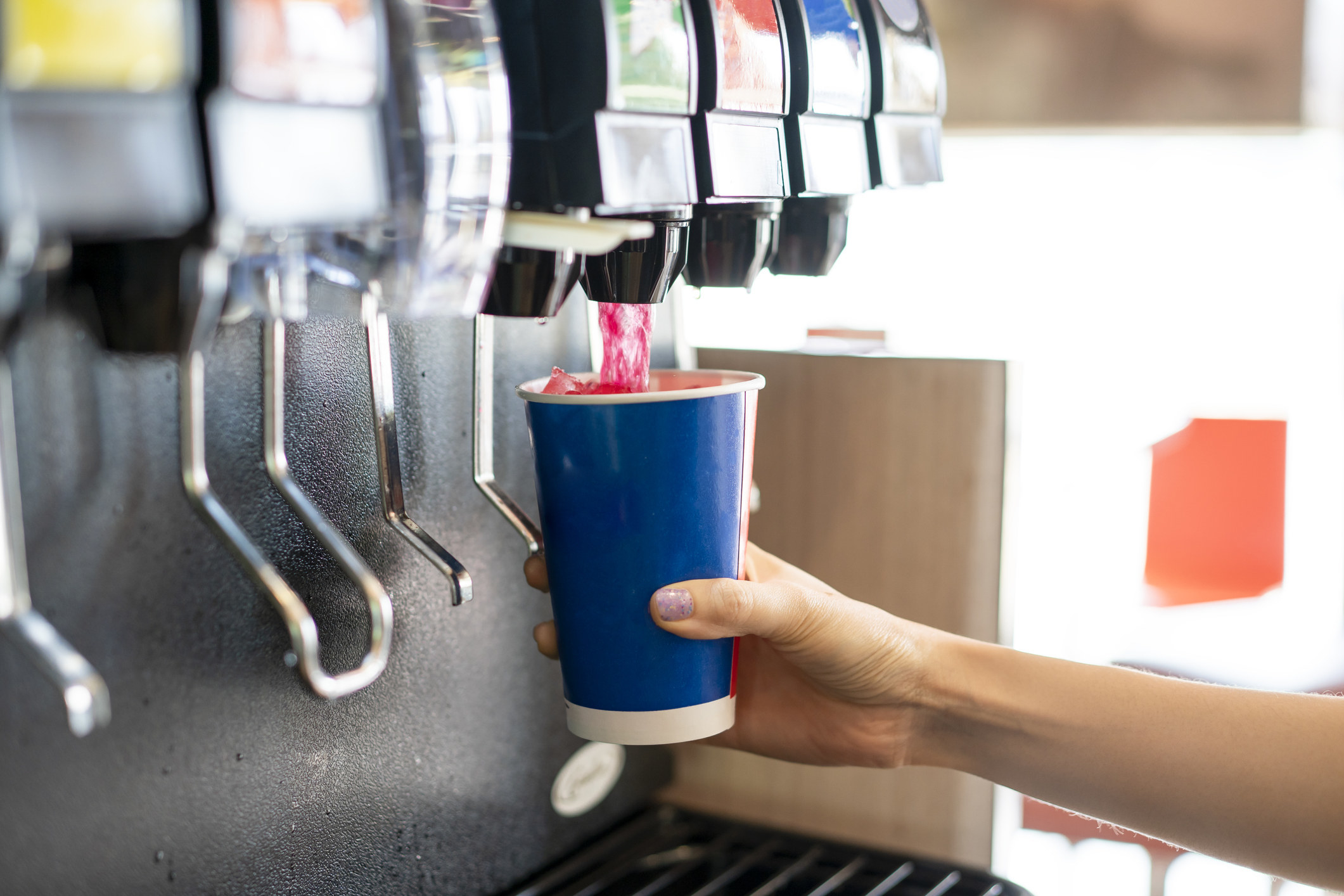 Someone pouring a soda from a soda machine.