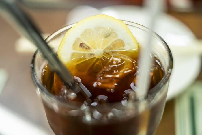 A glass of soda with a lemon slice.