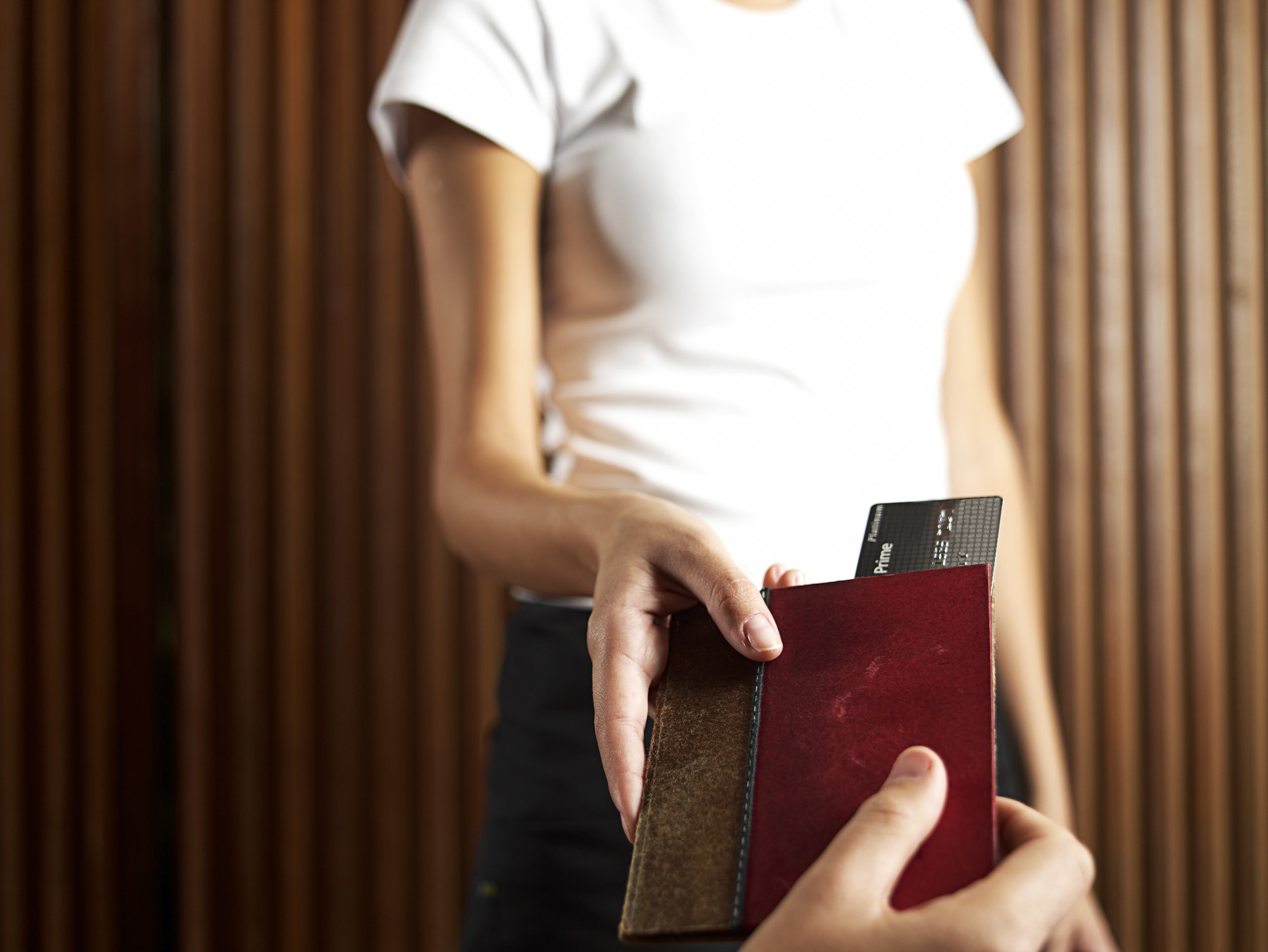 A waiter taking a check with a credit card.