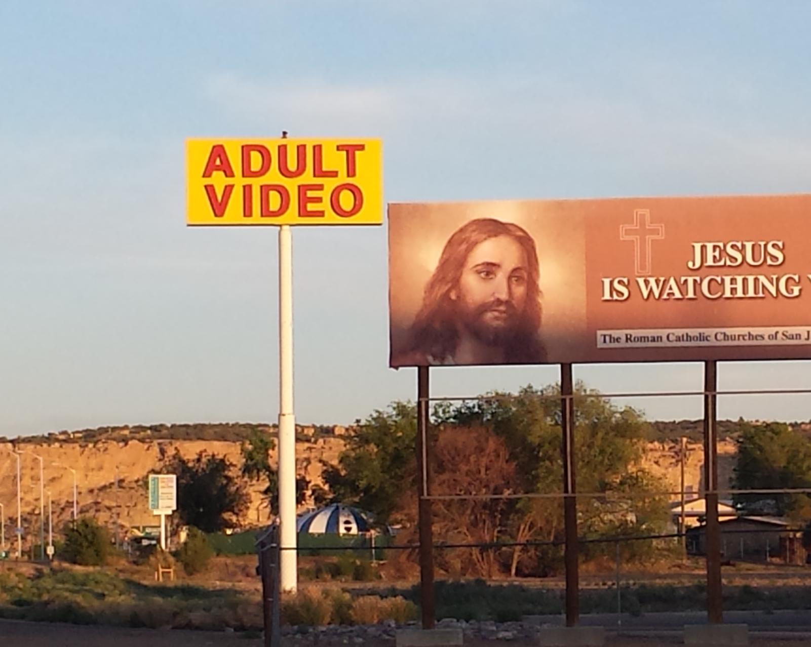 An adult video billboard next to a Jesus billboard.