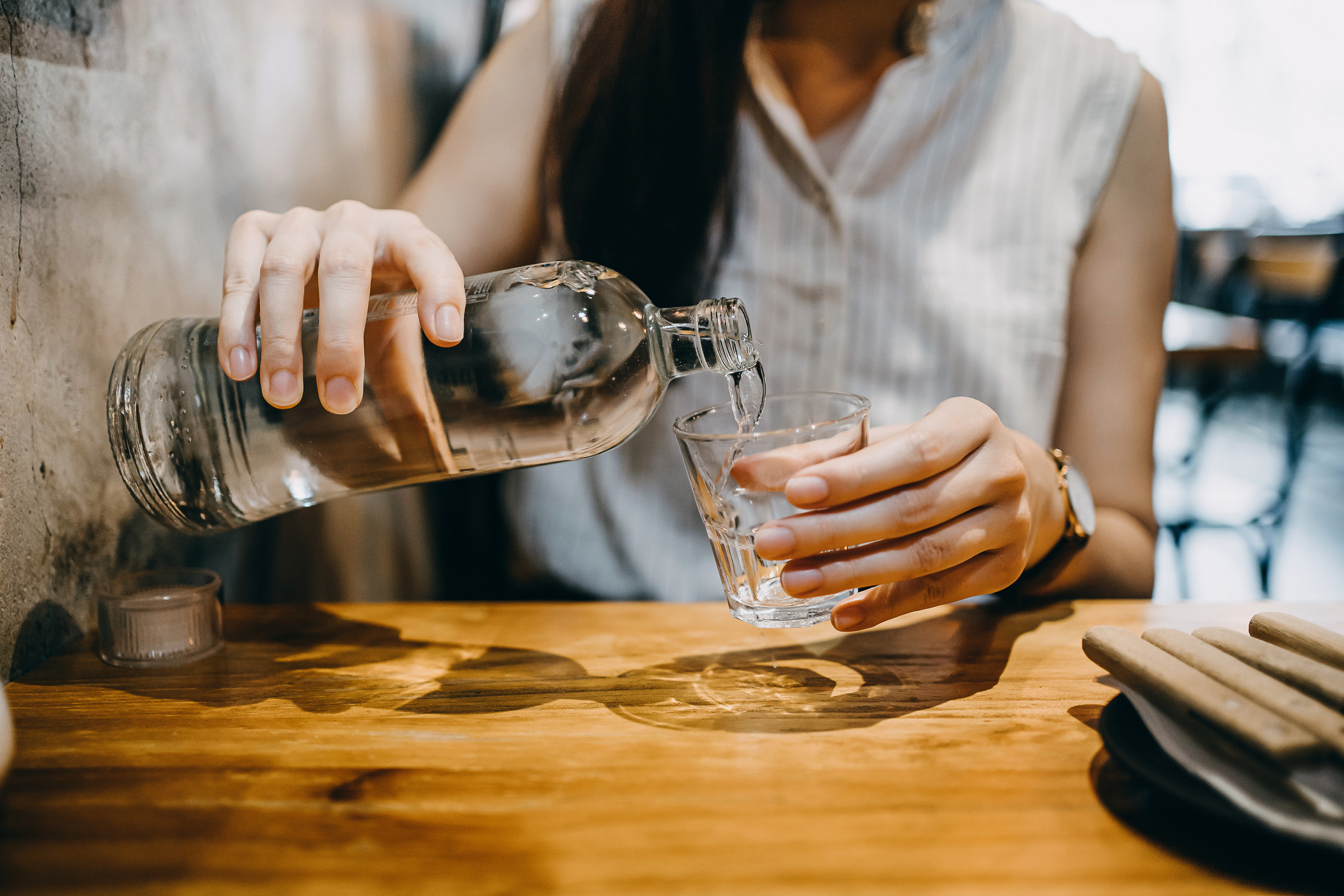 A woman pouring a pitcher of water into her glass.