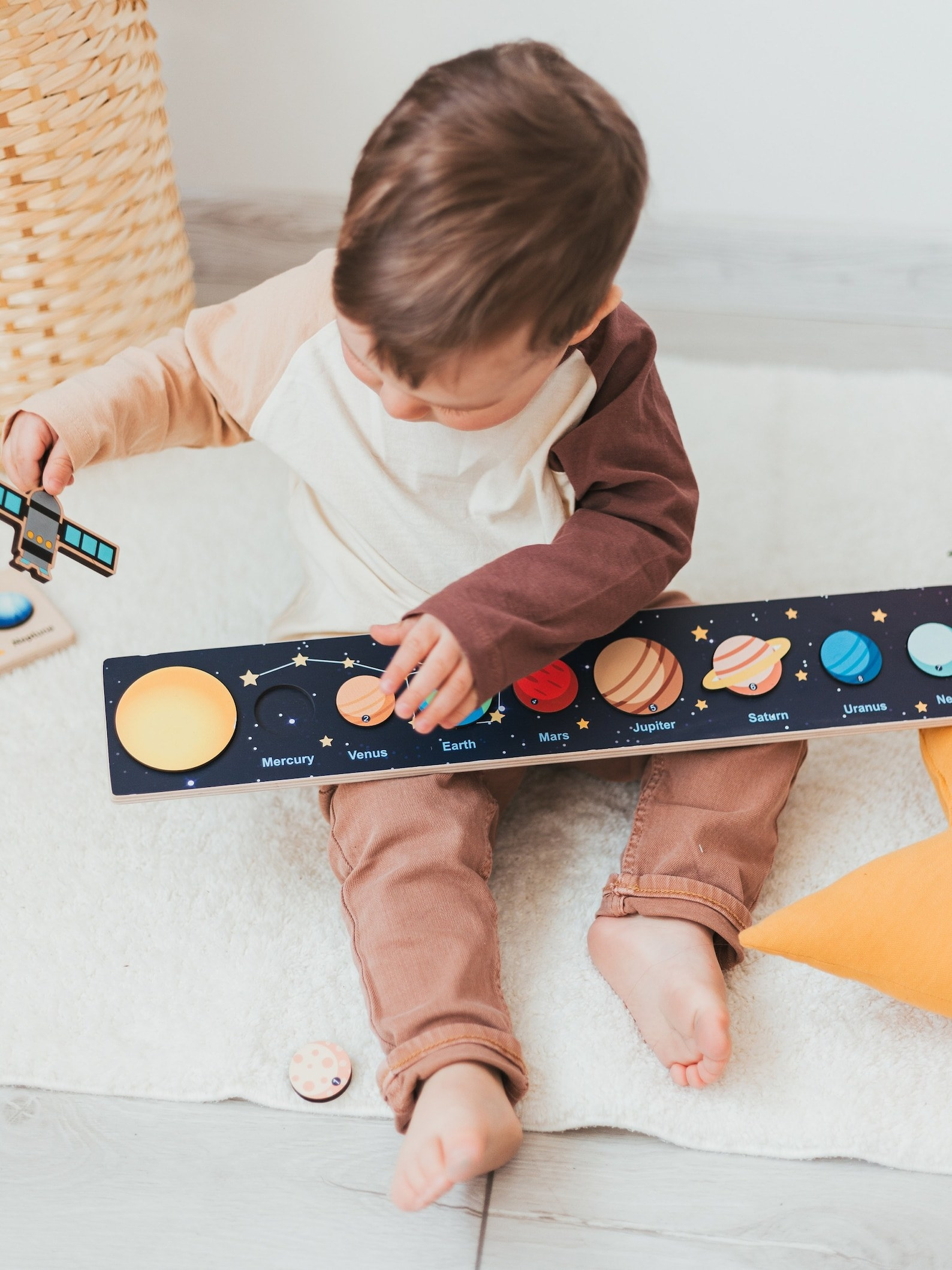 A child playing with the wooden solar system puzzle