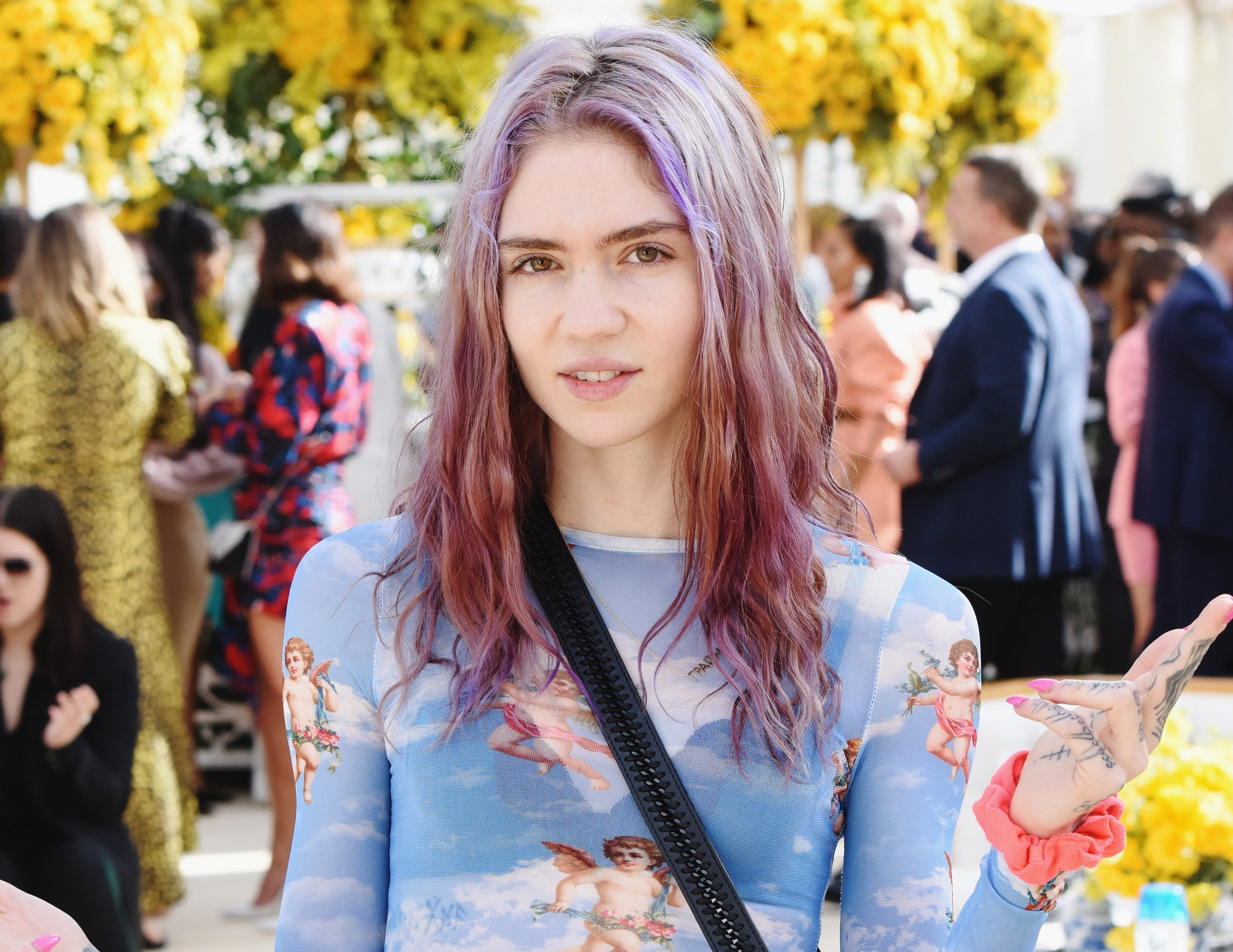 Grimes wears a sheer blue top with angels printed on it