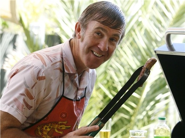 Kel Knight holding up tongs over a BBQ