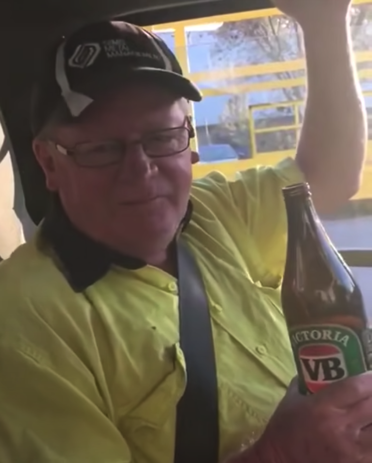 A tradie holding a long neck VB while sitting in a car