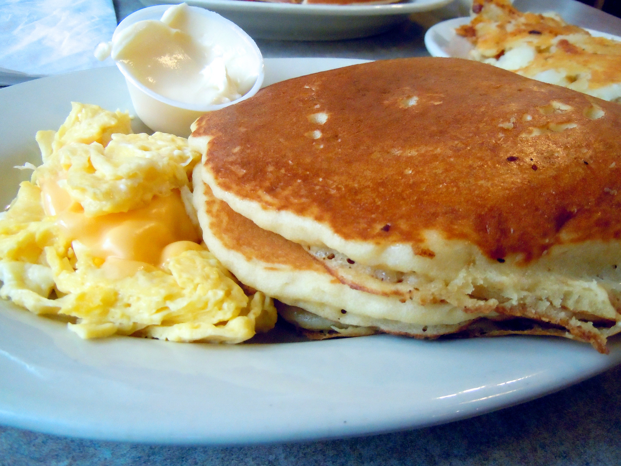 A stack of pancakes with eggs.