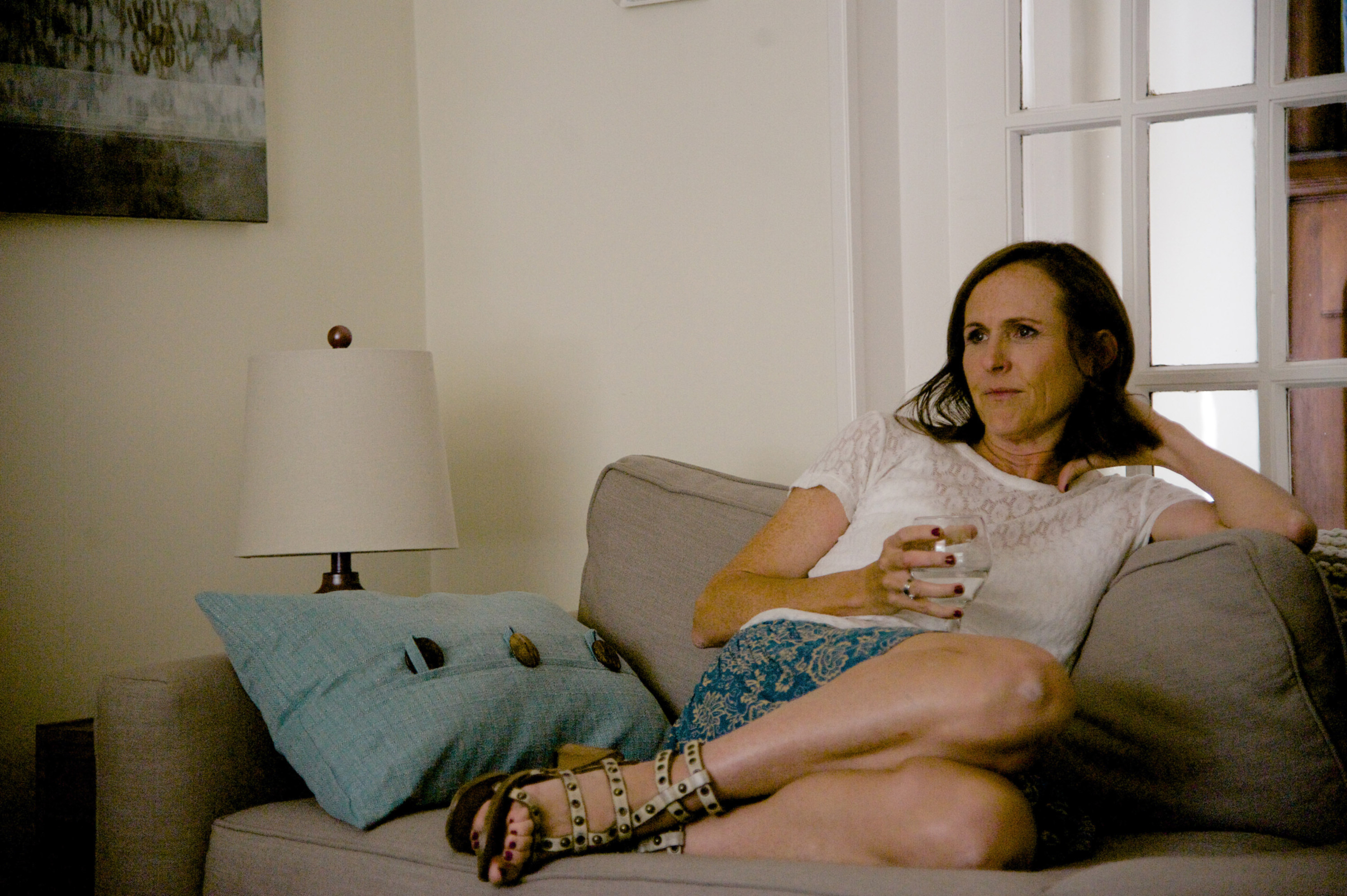 Molly Shannon sits on a couch with a glass of water