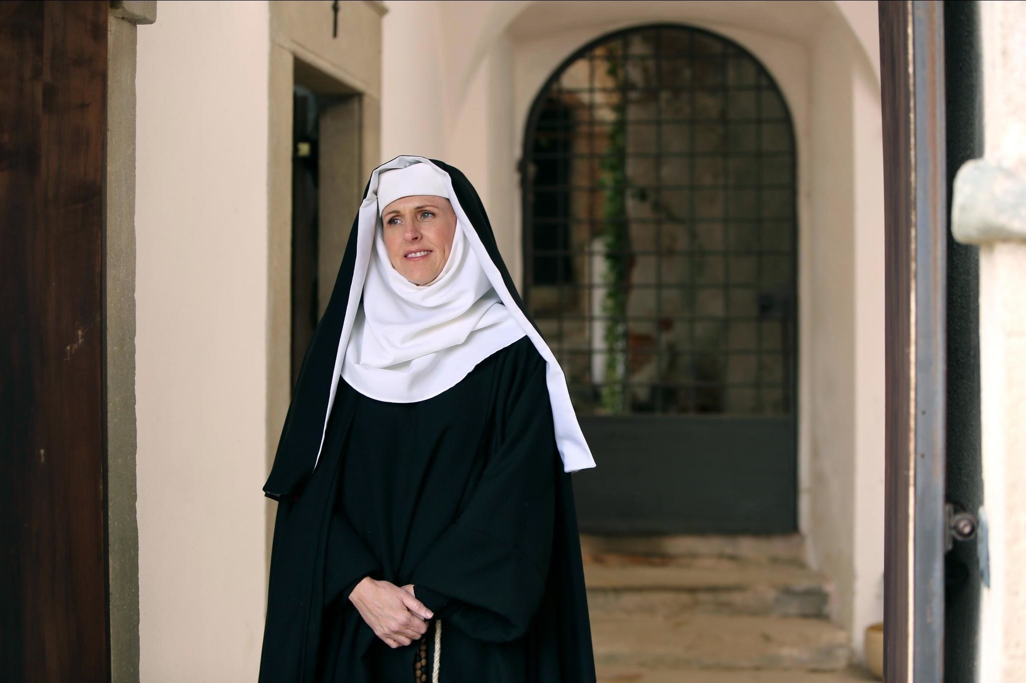 Molly Shannon stands dressed as a nun