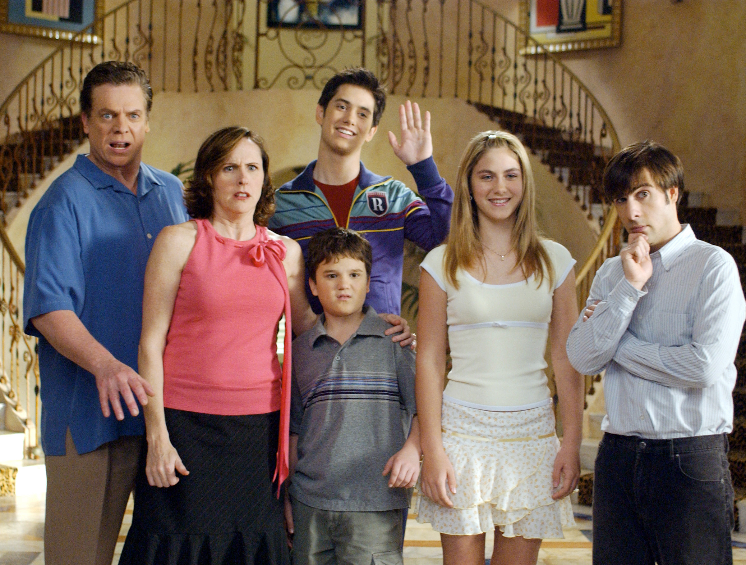 Chris McDonald, Molly Shannon, Jake Sandvig, Bret Loehr, Caitlin Wachs, and Jason Schwartzman stand in the foyer of a mansion