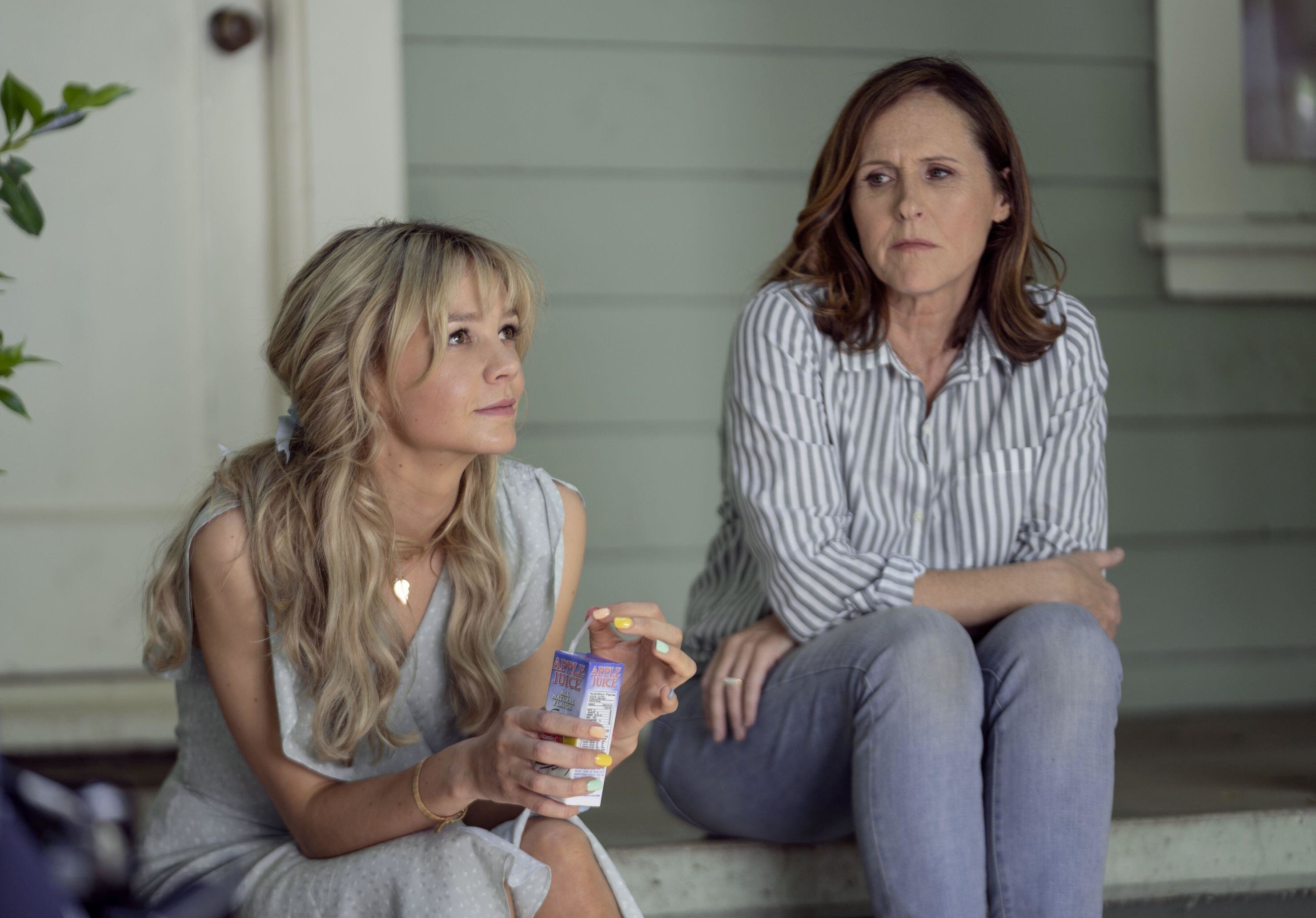 Carey Mulligan drinks a juice box as she talks with Molly Shannon on a front porch