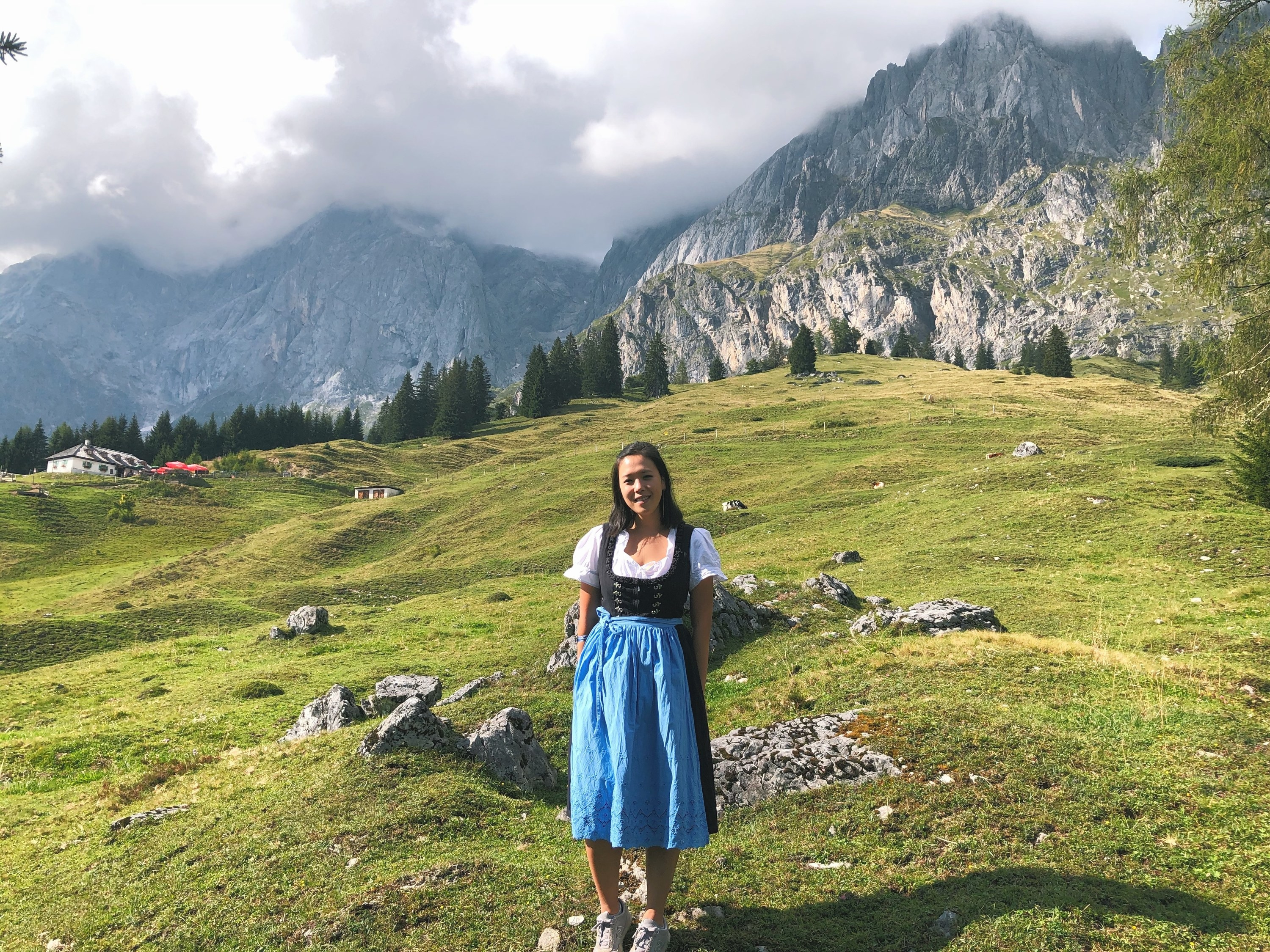 The writer wearing a traditional dirndl, standing in front of a lush mountain top