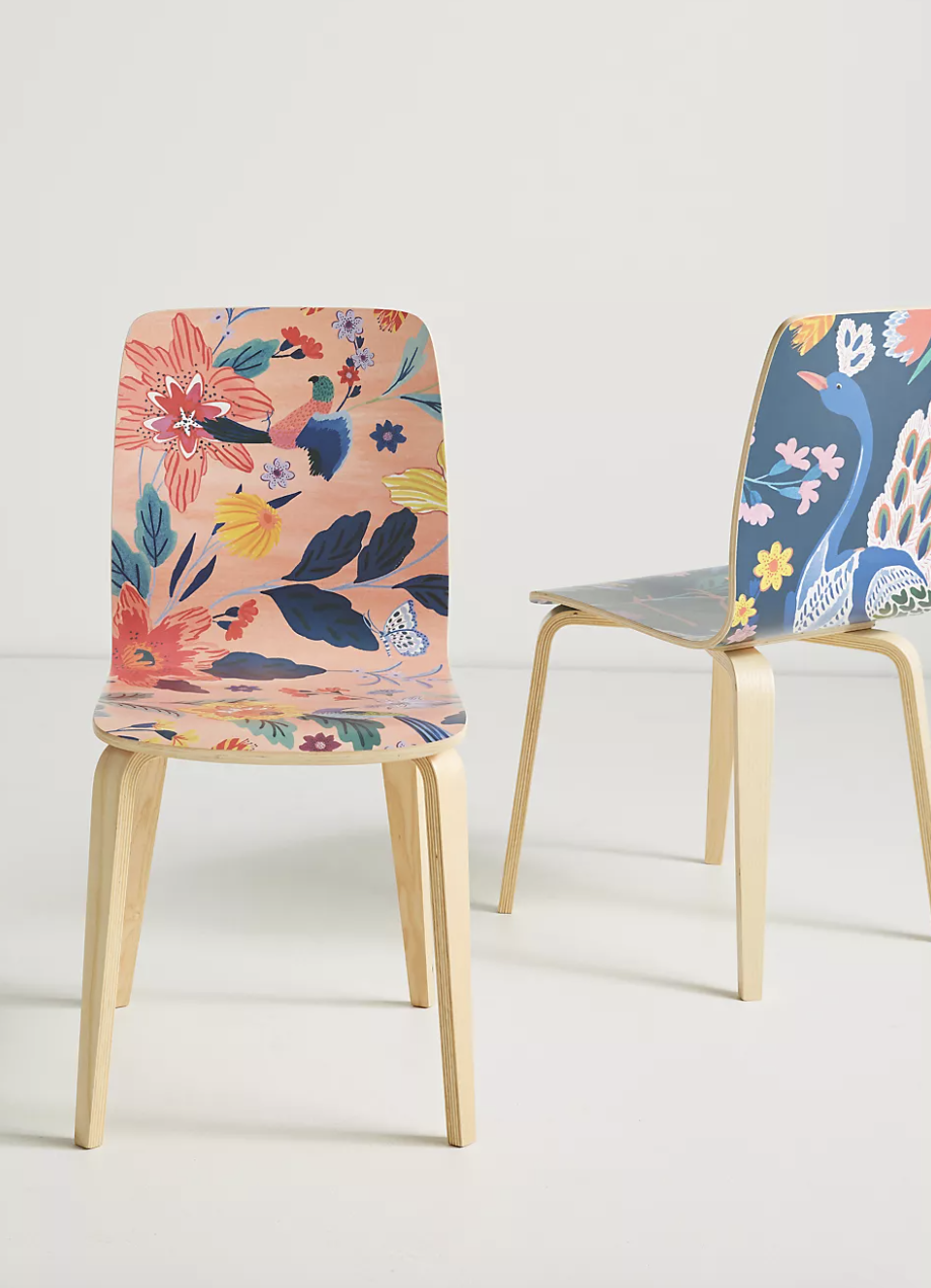 a pink floral wooden chair next to a similar one in blue