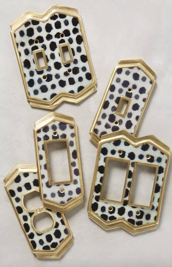 an array of light switches with black polka dots on them and gold edges