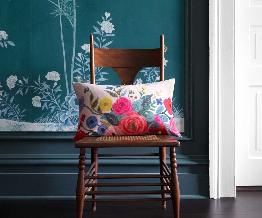 a long horizontal pillow with brightly colored florals sitting on a chair