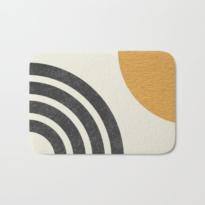 a white rectangular bath mat with gray and yellow shapes on it