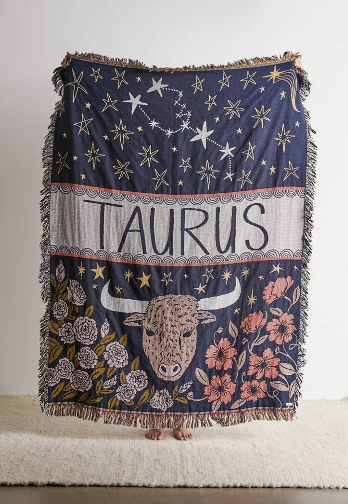 a fringed throw blanket with a taurus-inspired design on it and florals