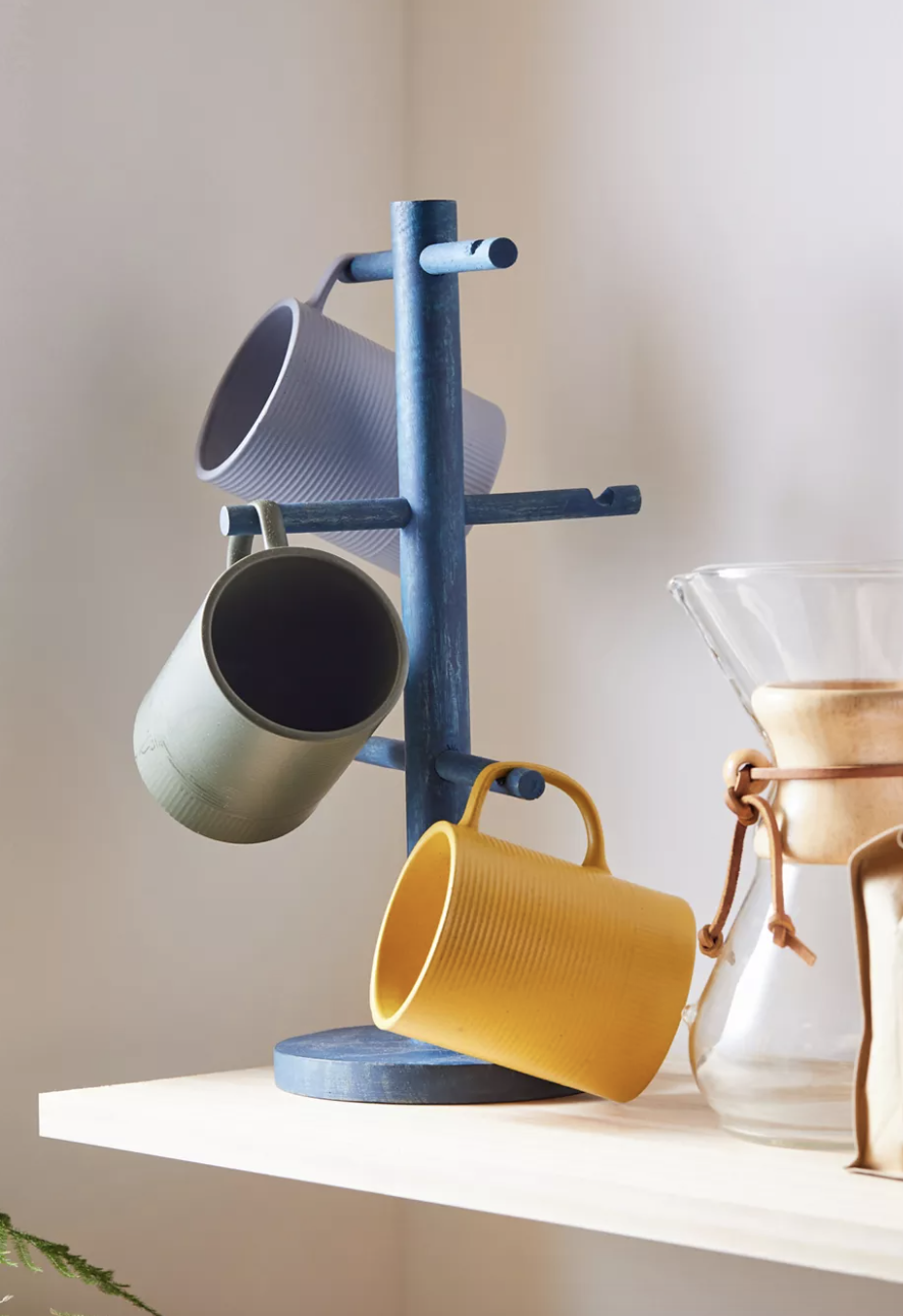 three mugs hanging from a blue mug stand with various perches