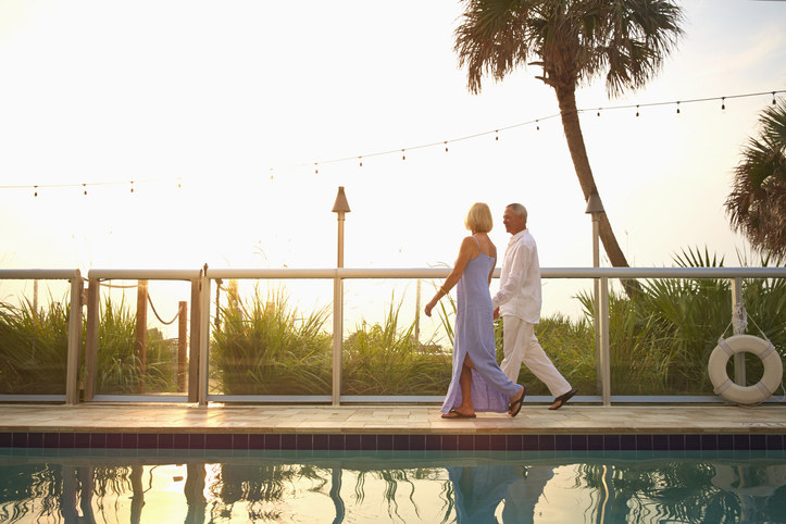 old couple walking by a pool