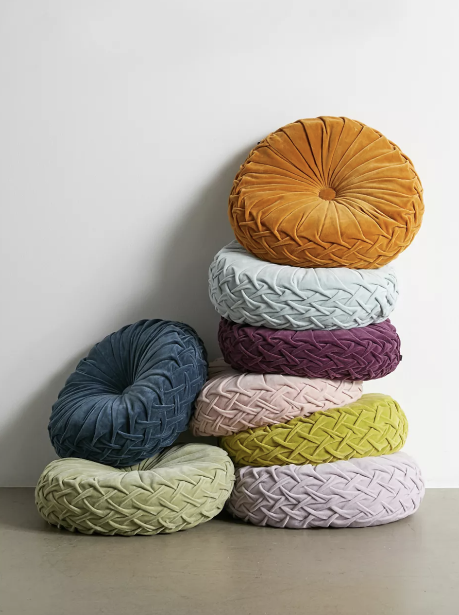 a stack of colorful round pillows