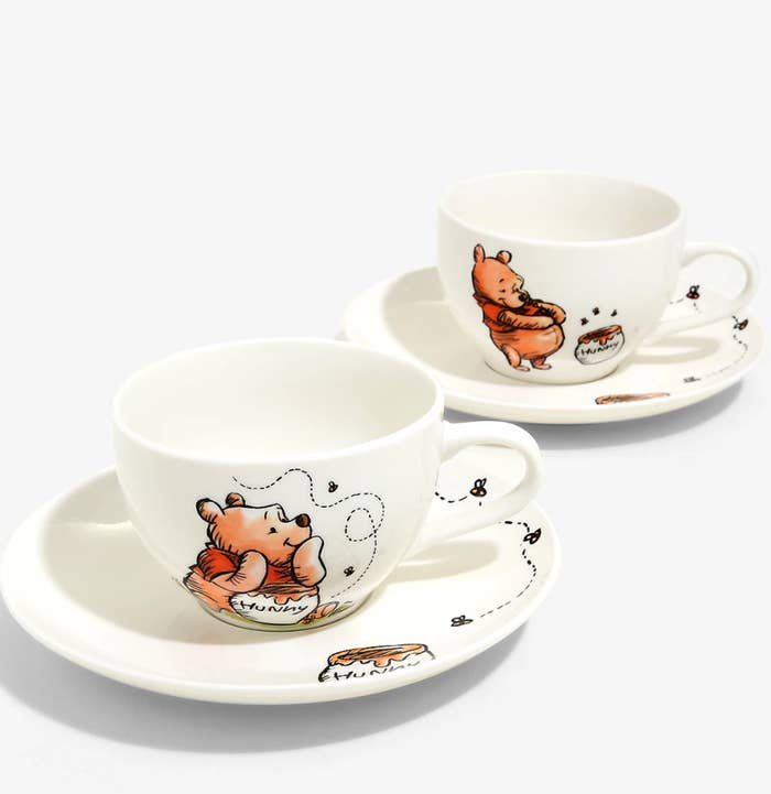 two winnie the pooh themed tea cups and saucers