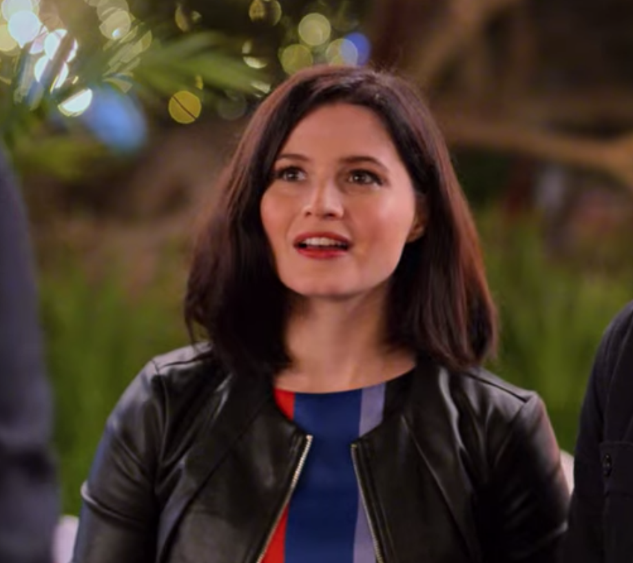 Rachel wears a striped blouse under a leather jacket