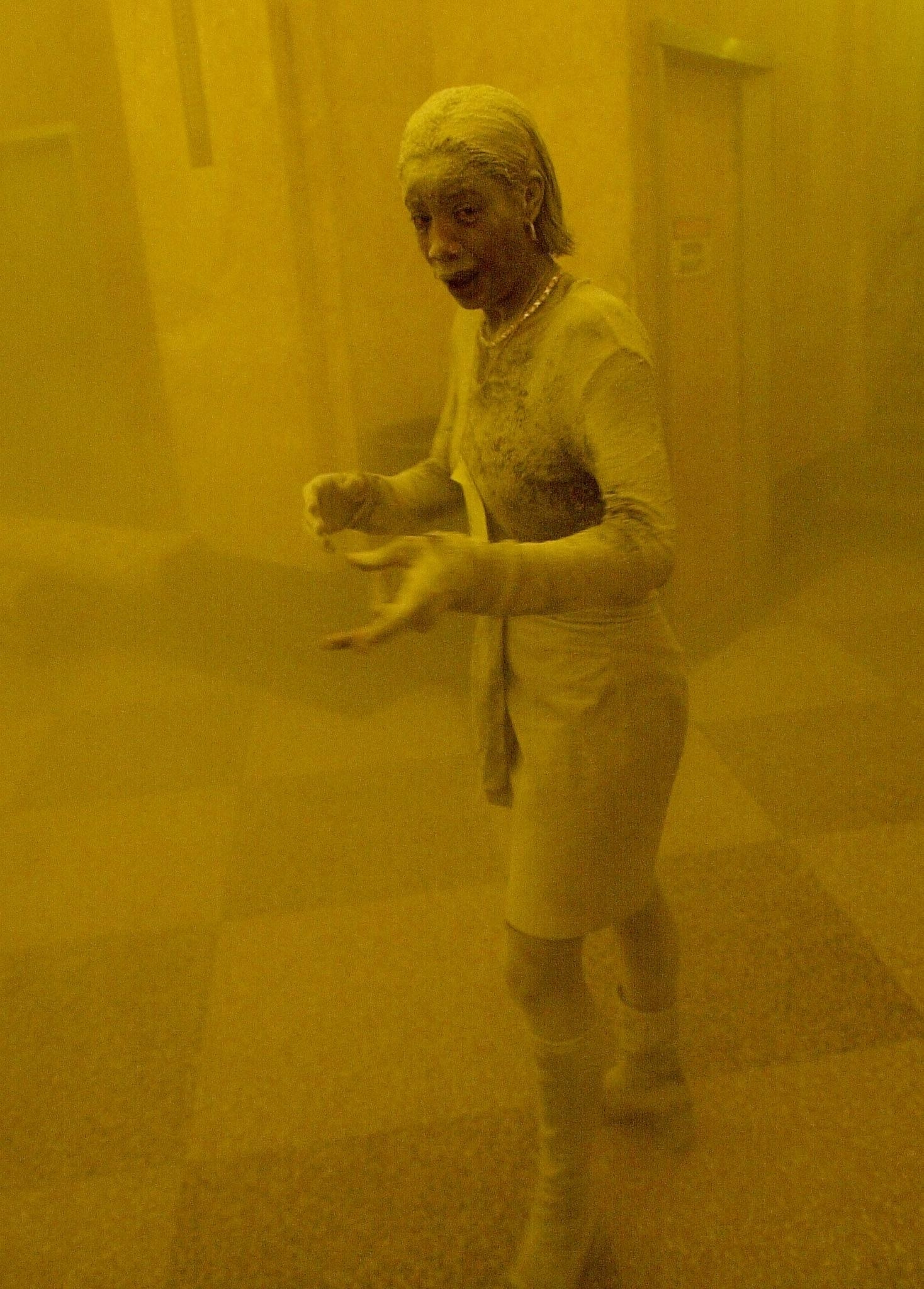 A woman completely covered in ash and in apparent distress in a building lobby that is yellow and hazy from the ash and smoke