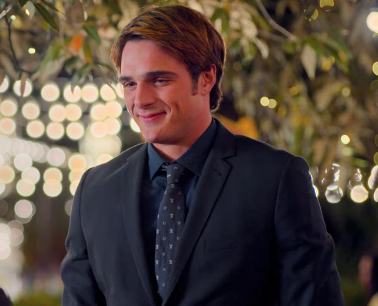 A close-up of Noah as he wears a dark suit and matching tie