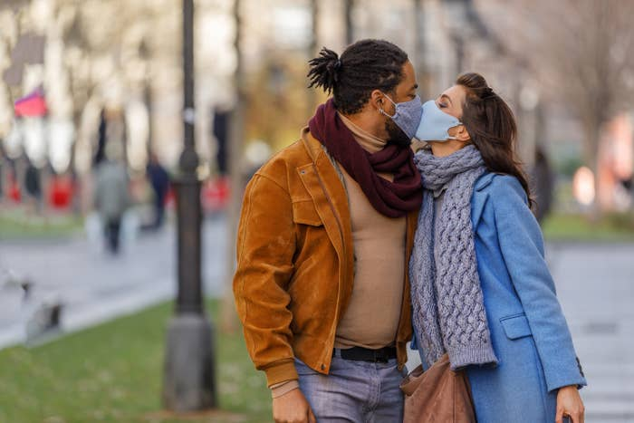 Photo of two people wearing face masks kissing