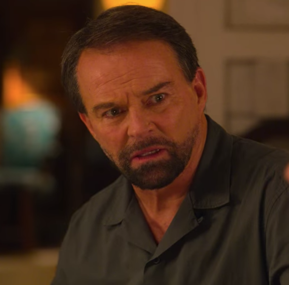 Mike wears a dark-colored button-up shirt and a hurt expression on his face