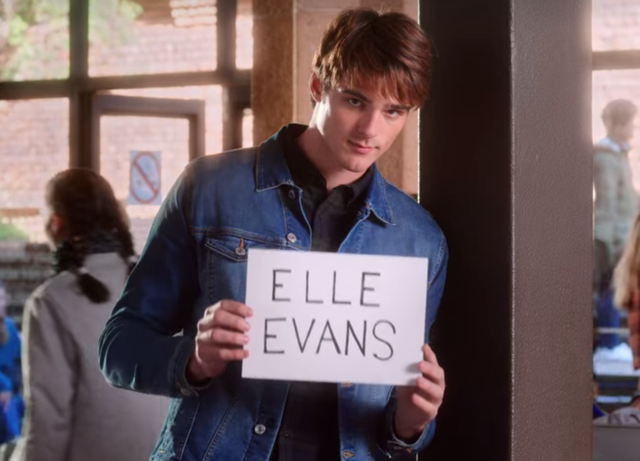 Noah holds up a sign with Elle's name on it as he waits in a crowded airport