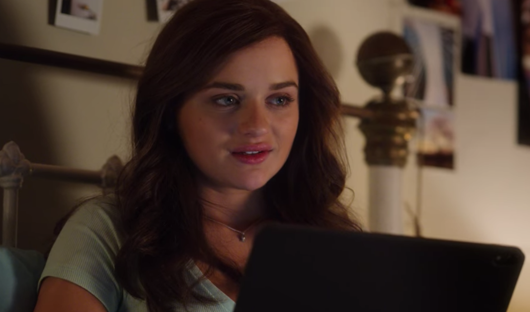 A close-up of Elle as she looks away from her laptop screen