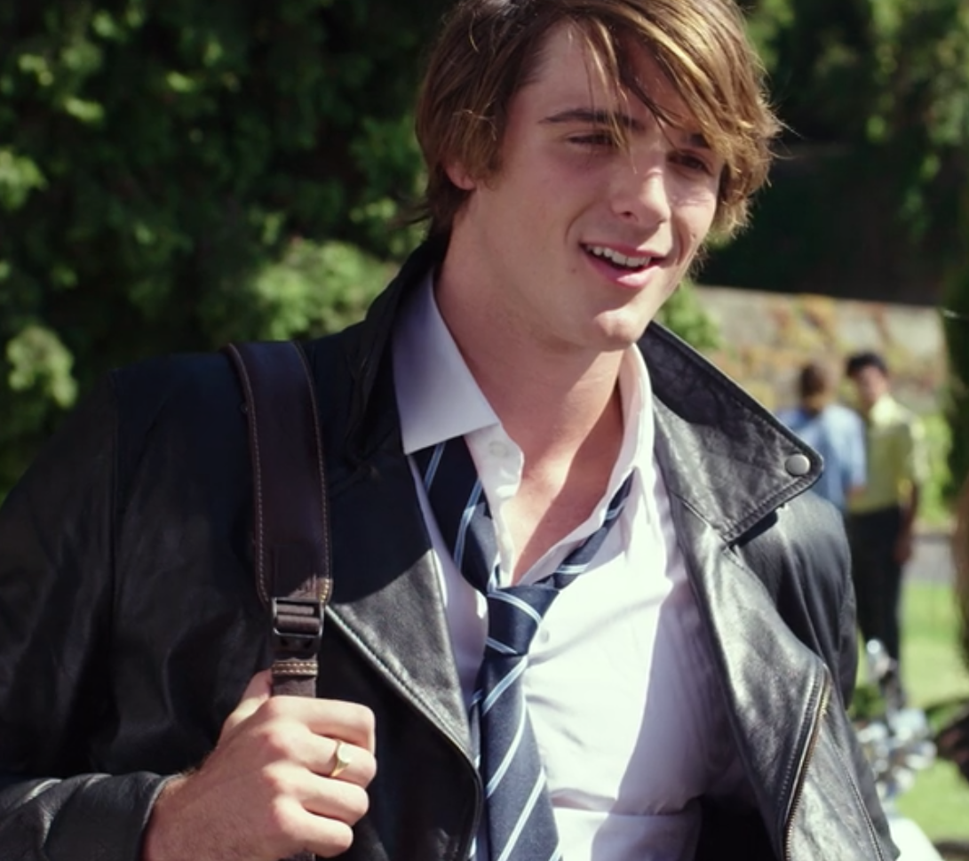 Noah wears a button-up shirt, a striped tie, and a leather jacket
