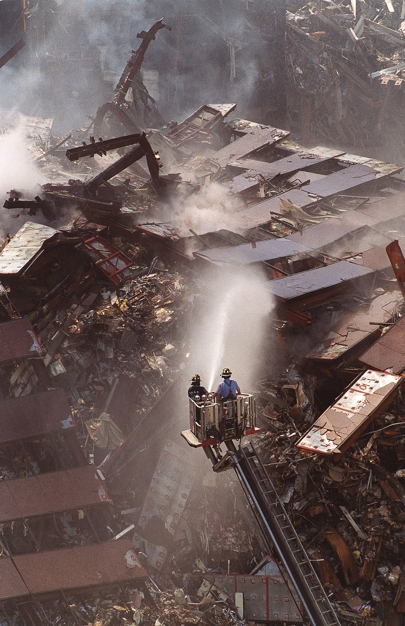 Two firefighters on a platform crane above a mountain of wreckage