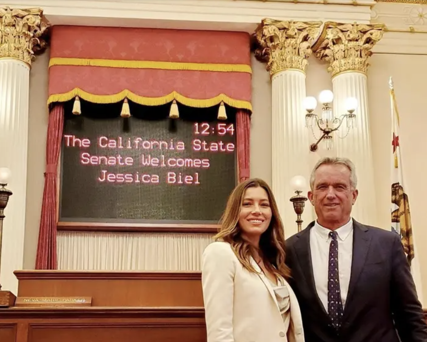 """Jessica standing with Robert F. Kennedy Jr. in front of a sign saying """"The California state senate welcomes Jessica Biel"""""""