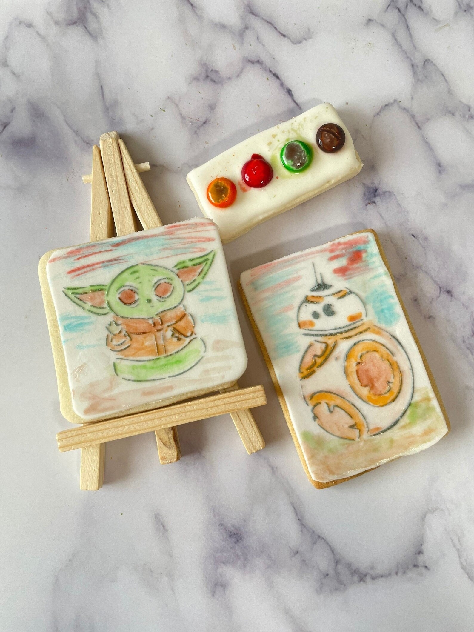 two cookies with a star wars character on each. they have been painted with m&m chocolates that are placed on a third cookie to look like a painting pallet. it comes with a small wooden easel.