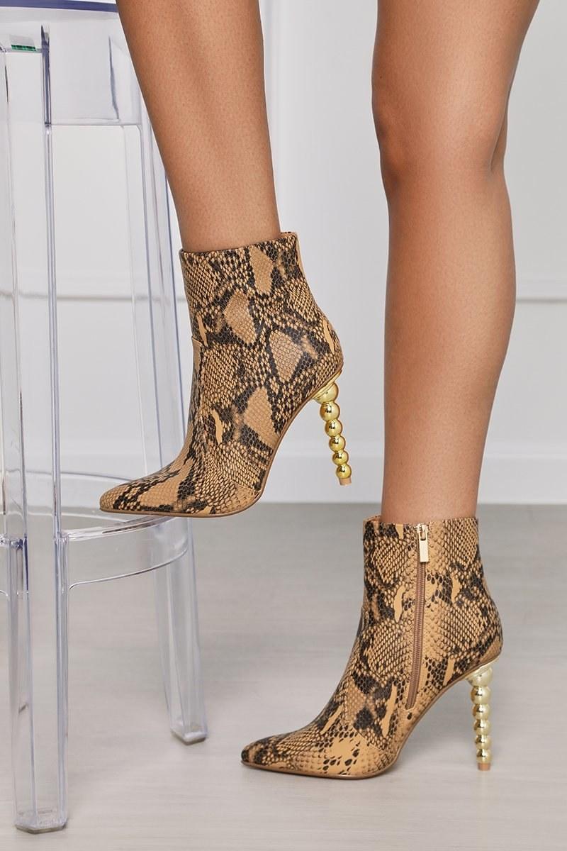 Model wearing snake print boots