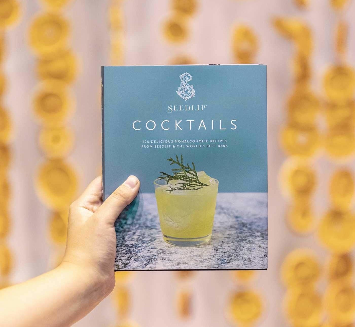 A person holding up a book titled seedlip cocktails