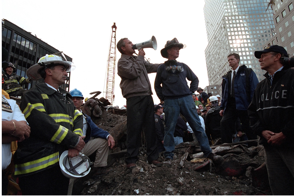 President George W. Bush stands on the wreckage of the World Trade Center with a bullhorn speaking to rescue workers
