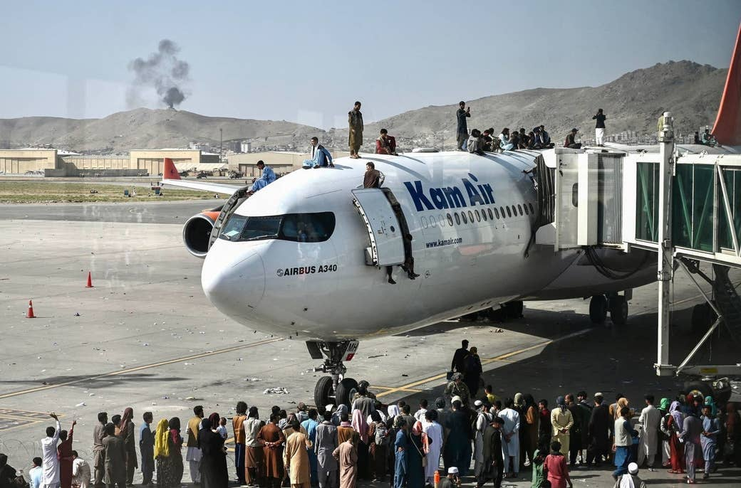 Afghan people climb atop a plane as they wait at the airport in Kabul