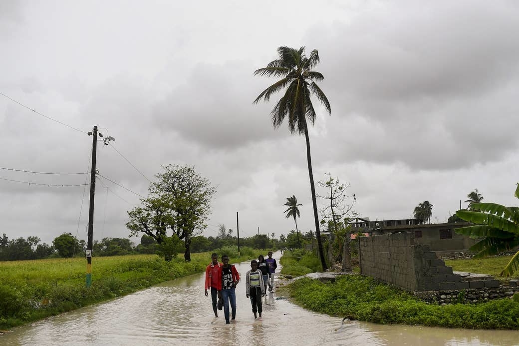 Residents of Haiti wade through a flooded road
