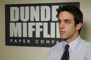 ryan howard standing in front of a dunder mifflin sign