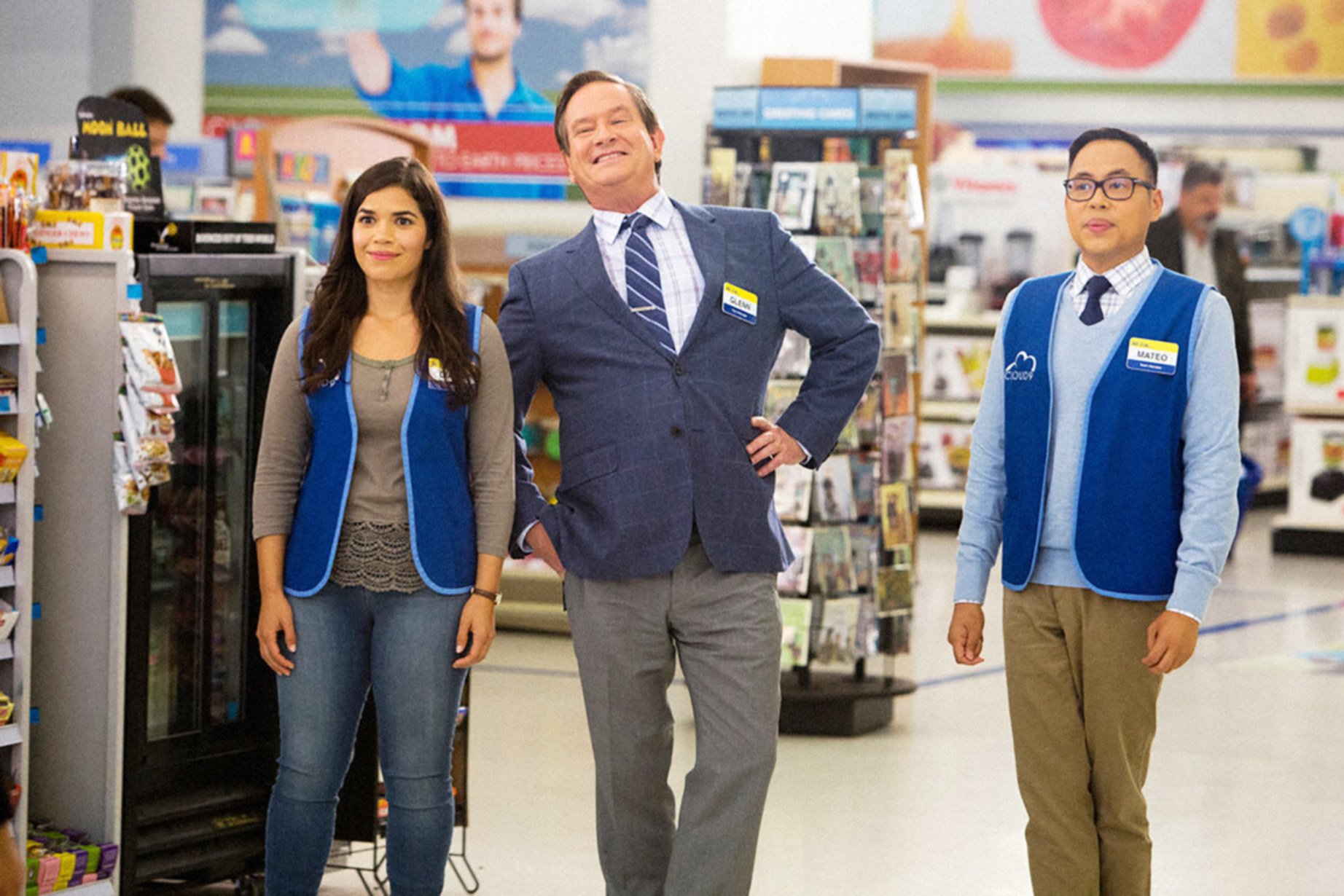 America Ferrera, Mark McKinney, and Nico Santos stand together in the aisle of their store