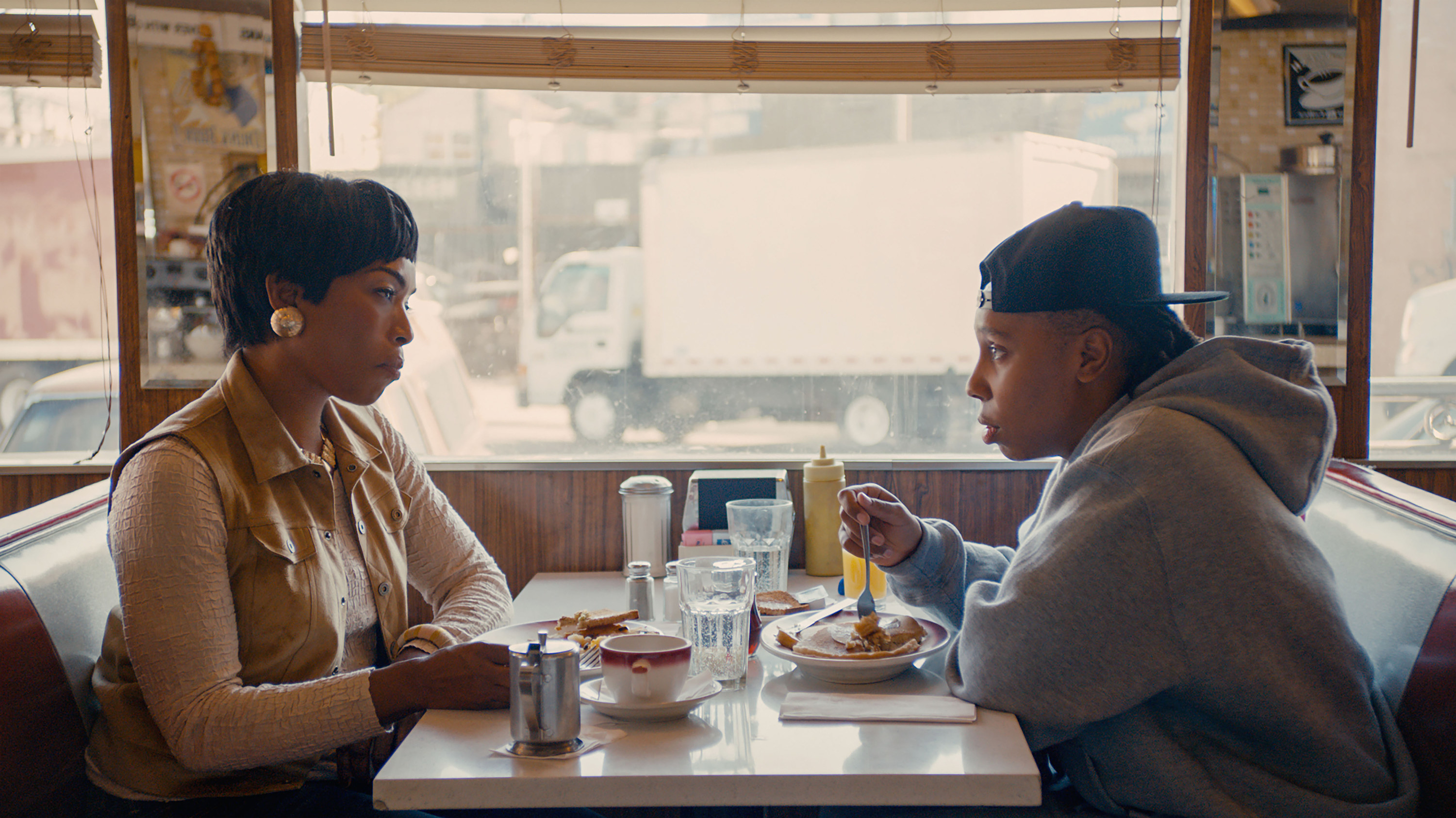 Angela Bassett and Lena Waithe sit across from each other at a diner