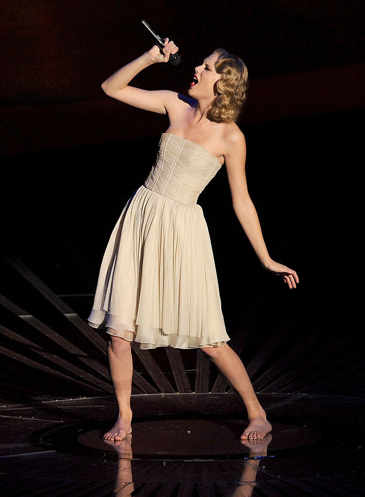 Taylor Swift in a beige dress performing barefoot