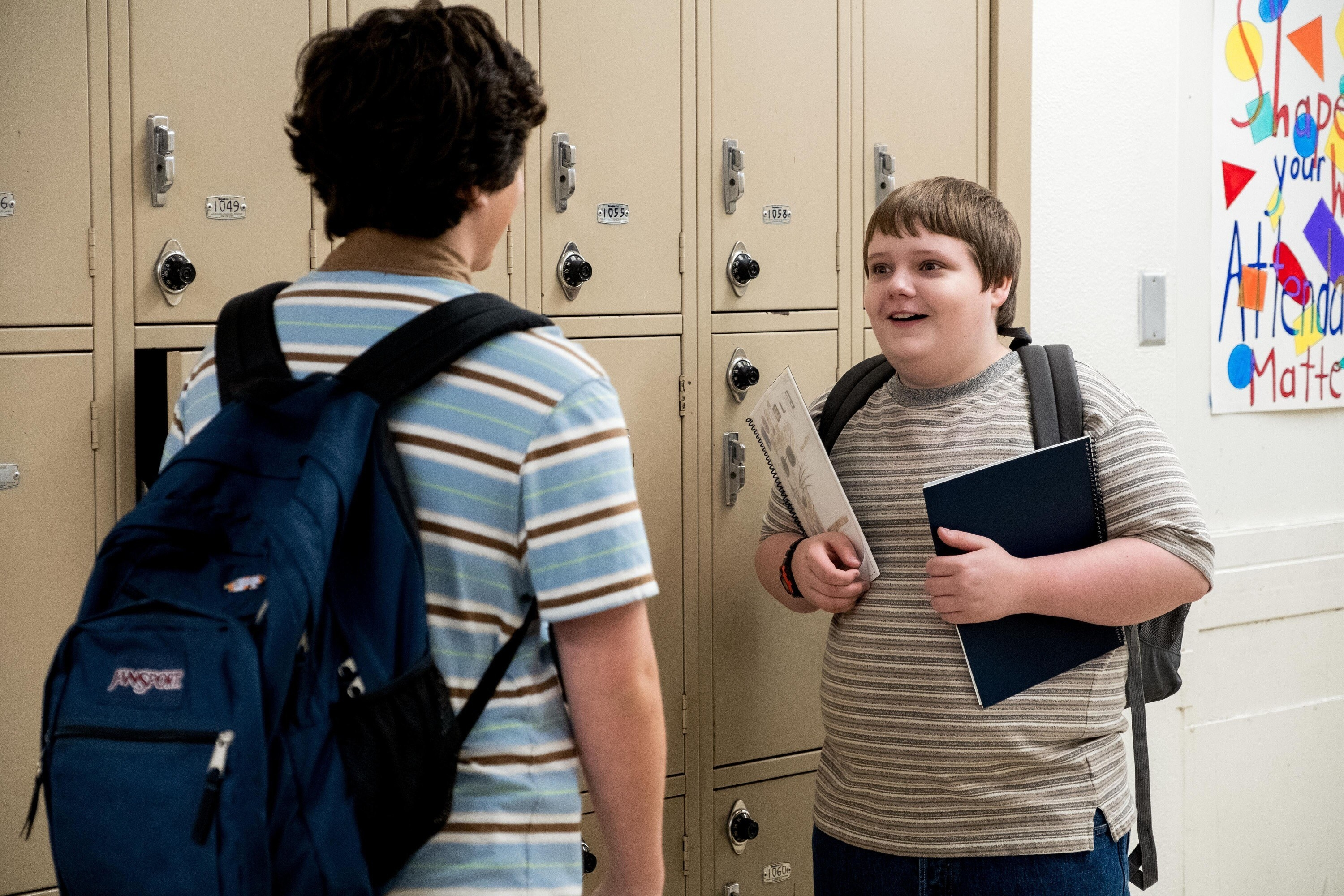 Taj Cross and Dylan Gage talk to each other next to their lockers