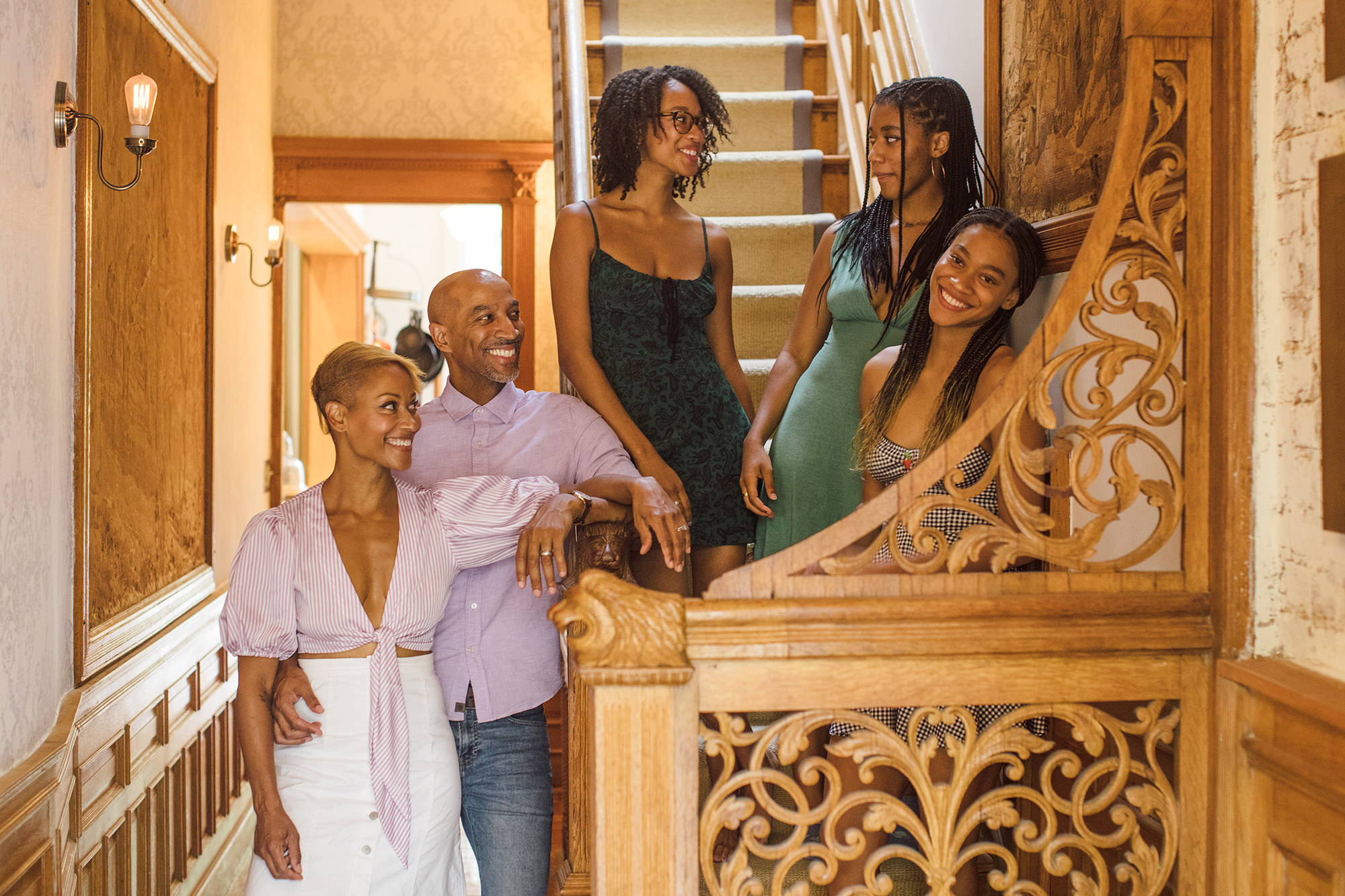 A husband and wife and their three daughters, all smiling, in their stairwell in Brooklyn